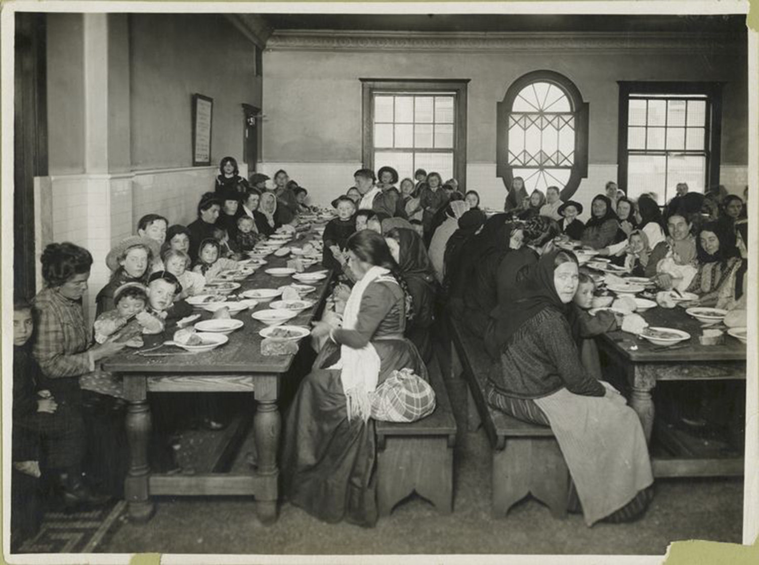 Uncle Sam, host. Immigrants being served a free meal at Ellis Island., Levick, Edwin, NYPL Digital Gallery, Public Domain Mark