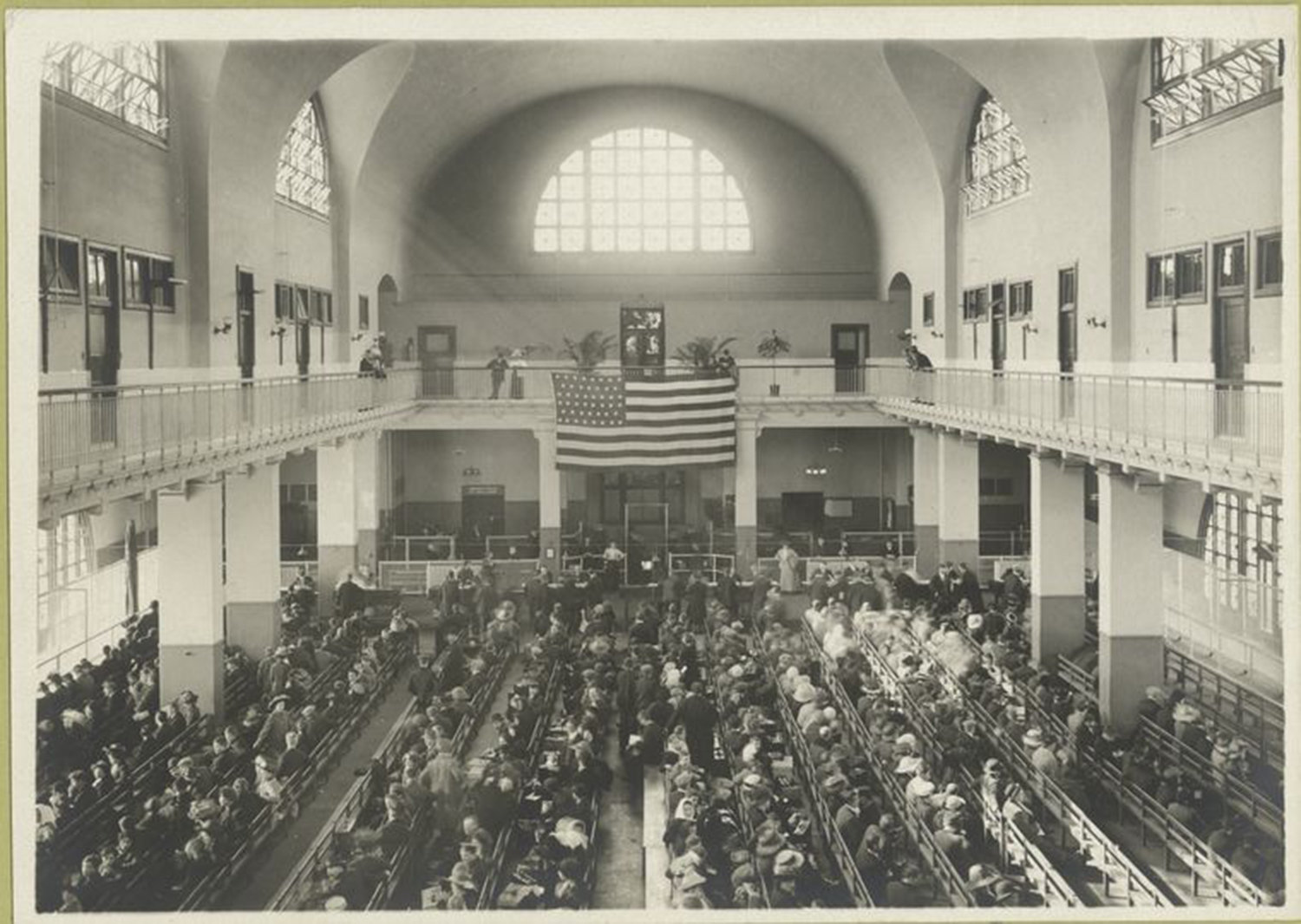 Immigrants seated on long benches, Main Hall, U.S. Immigration Station., Williams, William (1862-1947), NYPL Digital Library, Public Domain Mark