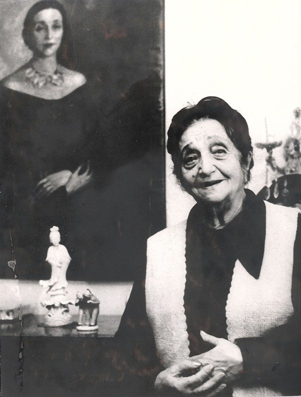 Dora Gabe in front of the portrait of herself by H. Risca, 1980s, Unknown photographer, Dora Gabe Public Library - Dobrich, CC0