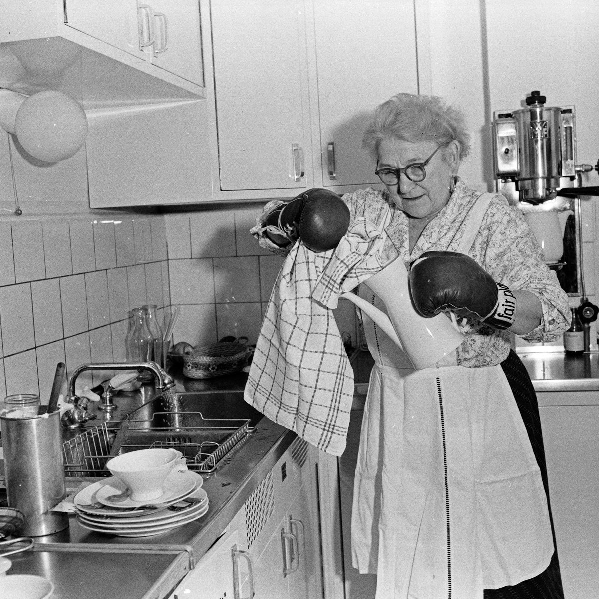 The housekeeper of German comedian Peter Frankenfeld doing the dishes with boxing gloves, 1950s, Siegfried Pilz, United Archives, In Copyright