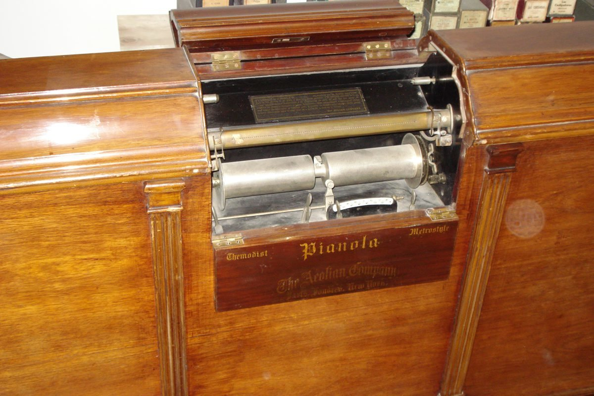 Detail of a pianola showing the perforated brass bar, over which runs the paper pianola roll., Æolian Company, Musée De La Musique Mécanique, CC BY-NC-SA