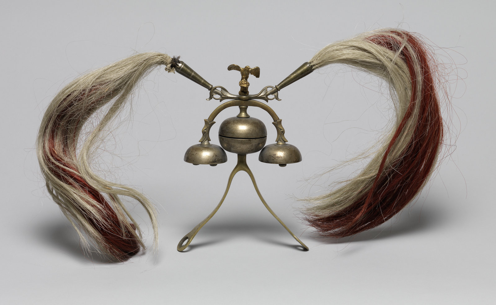 Sleigh bells, 1880/1890, Unknown, [These sleigh bells were mounted on a horse collar for winter sleigh rides in the countryside. The ringing bells warned pedestrians of an approaching sledge gliding silently in the snow. They were also a form or personalisation for their owner, a Franconian country-nobleman. The frame is made of brass, originally silver-plated, and the bells of bell-metal, a hard alloy used for making bells. The decorative feather bushes are made from horsehair coloured in the Franconian red and white.], Germanisches Nationalmuseum , CC BY-NC-SA