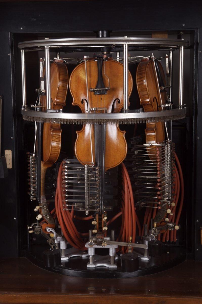 Detail of a phonoliszt violina, showing the violins bowed by a large rotating wheel., Hupfeld - Rönisch, Musée De La Musique Mécanique , CC BY-NC-SA