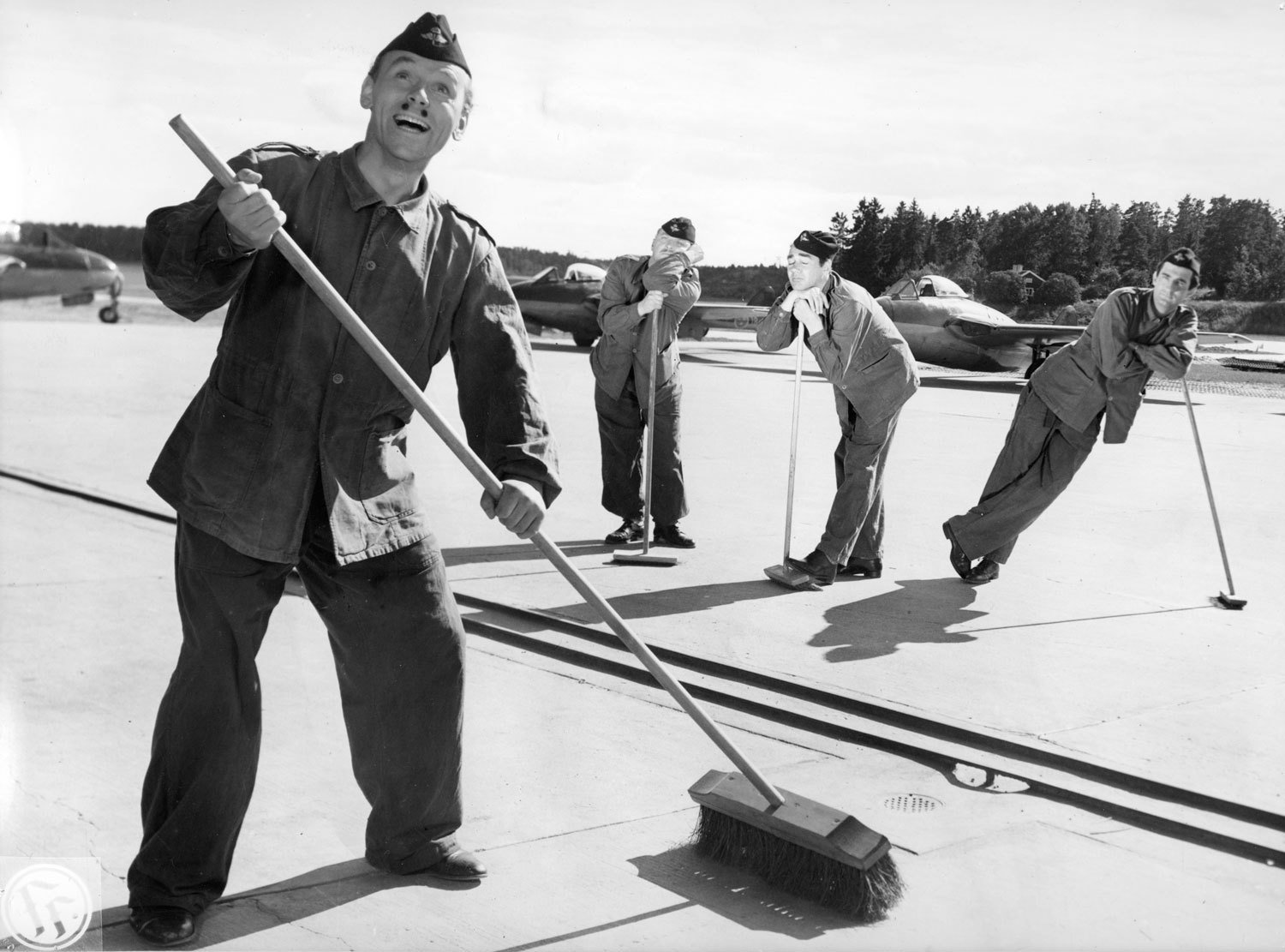 Actor Nils Poppe sweeping the tarmac in 'Flyg-Bom', 1952, Unknown, Kulturmagasinet, Helsingborgs museer, Public Domain Mark