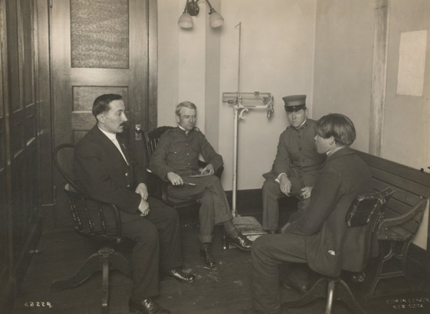 A private interview between a young immigrant and an Ellis Island official, A private interview between a young immigrant and an Ellis Island official. Two staff members [?] are also present., Levick, Edwin, NYPL Digital Library, Public Domain Mark