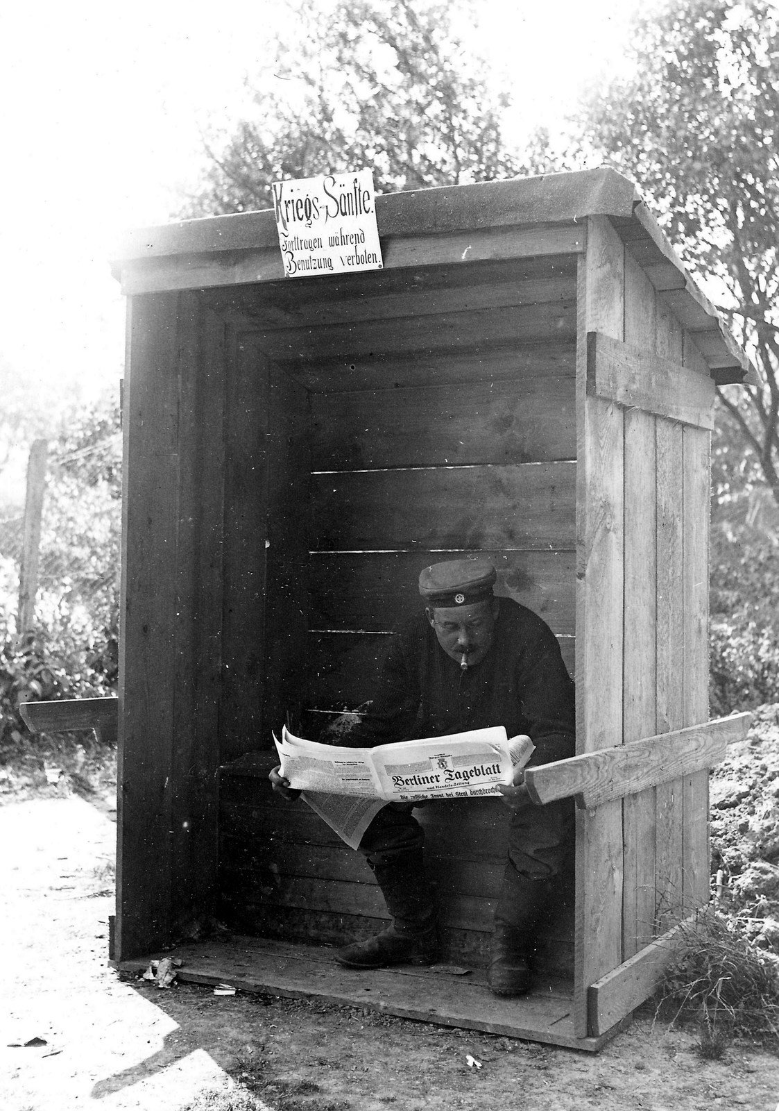 A soldier smoking a cigar and reading a newspaper while seated on a latrine , photographer unknown, Rolf Kranz  / Europeana 1914-1918, CC BY-SA