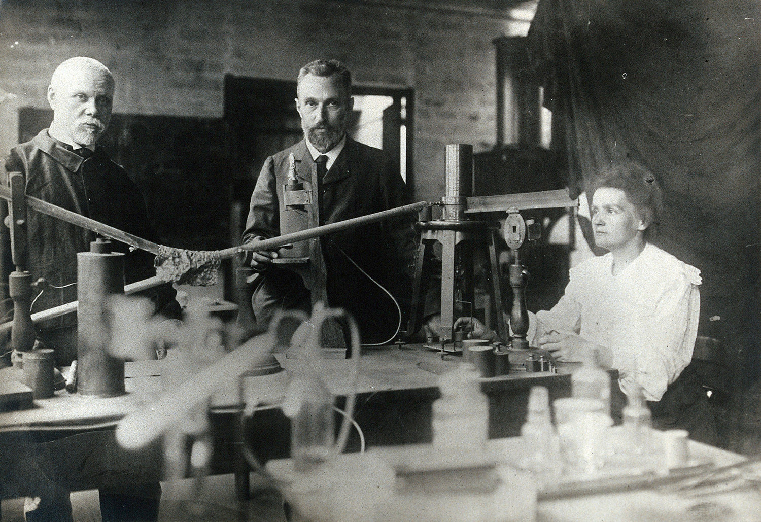Marie and Pierre Curie (centre) with a man, using equipment in their laboratory, Paris, ca. 1900, Unknown photographer, Wellcome Collection, CC BY